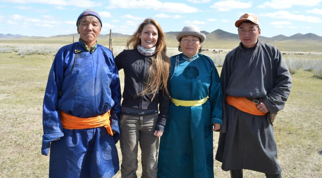 Female Culture and Community Volunteer poses with Mongolian Nomads during a Volunteering project.